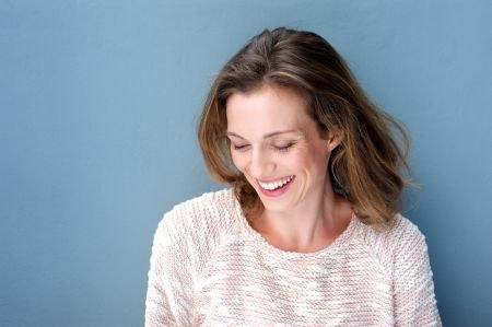 lachende Frau vor blauer Wand