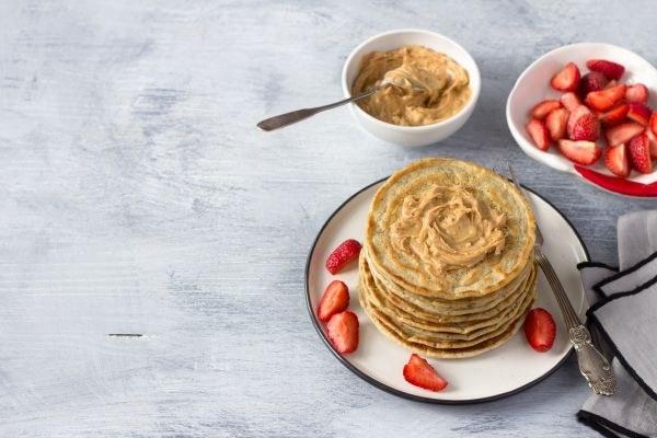 gestapelte Pancakes mit Erdbeeren und Nussmus