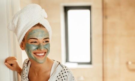lachende Frau mit Handtuchturban und Maske im Gesicht