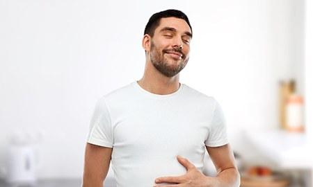 Mann mit geschlossenen Augen mit Hand auf Bauch gelegt